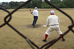 """A Belleville Stags catcher watches as a St. Louis Unions player """"strikes the ball"""" during a game on August 4, 2012 at the Swansea Moose Lodge fields.  The teams played by rules of the game as they were in the late 19th century -- when there were no umpires, only a lone arbiter to make judgement calls."""