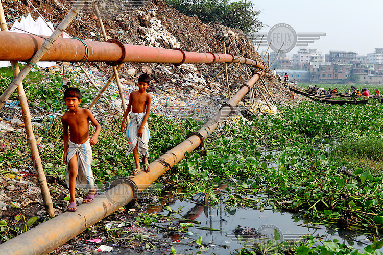 Two boys use a pipeline to traverse the heavily polluted banks of the Buriganga River. Everyday 1.5 million cubic metres of waste water from 7,000 industrial units in surrounding areas and another 0.5 million cubic metres from other sources are released into the river. Although the government have enacted laws that require industry to safely process effluents these are rarely enforced and pollution remains uncontrolled. The river is biologically dead and increasingly a serious health hazard to those using and living near it.