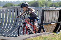 NWA Democrat-Gazette/DAVID GOTTSCHALK Jacob Campbell, 10, rides through a feature Monday, July 8, 2019, during the Breakaway Cycling Team Bike Skills Training Camp at the Runway Bike Park at the Jones Center in Springdale. The two day camp emphasizes skills, etiquette and safety. Today the campers will be on the Greenway Trail System.
