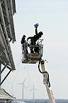 GERMANY Hamburg, IBA exhibition, an old war bunker is changed into an renewable energy project, installation of solar panels / DEUTSCHLAND  Hamburg, Energiebunker Wilhelmsburg , IBA Projekt, Energieerzeugung aus Solarenergie, Biogas, Holzhackschnitzeln und Abwaerme aus einem benachbarten Industriebetrieb, der Energiebunker soll einen Teil des Reiherstiegviertels mit Waerme versorgen und gleichzeitig erneuerbaren Strom in das Stromnetz einspeisen. Der Energiebunker soll circa 22.500 MWh Waerme und fast 3.000 MWh Strom erzeugen. Das entspricht dem Waermebedarf von circa 3.000 Haushalten und dem Strombedarf von etwa 1.000 Haushalten, Verkabelung und Montage der Solon PV Module an der Suedseite des ehemaligen Flakbunkers - MORE PICTURES ON THIS SUBJECT AVAILABLE!!