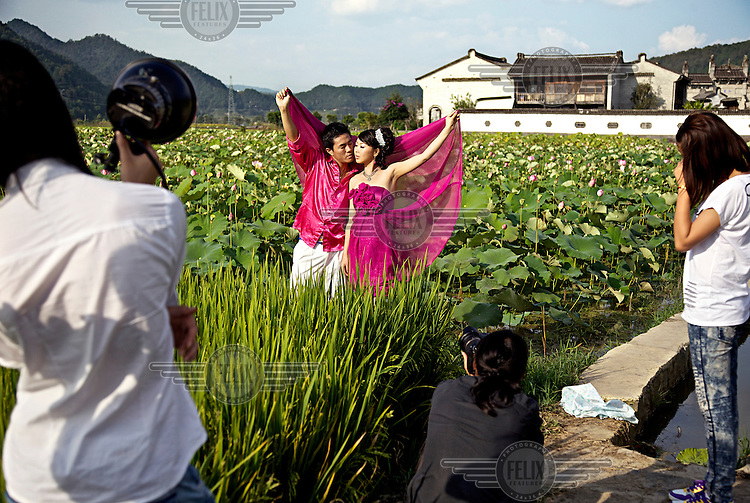 A couple are photographed for their wedding pictures standing in a lily pond in Heshun Ancient Town. /Felix Features