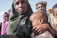 Kenya - Dadaab - A Somali refugee holding her baby in her arms is queuing for registration at Dadaab refugee camp.
