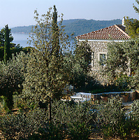 The villa is surrounded by trees and looks out over the Mediterranean