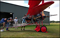 BNPS.co.uk (01202 558833)<br /> Pic: PeterBrueggemann/BNPS<br /> <br /> Peter fires up the engine...as volunteers hang on to the tail.<br /> <br /> The feared Fokker Dreidecker of the Red Baron has finally flown over Britian skies - after British based German doctor 'Baron' Peter von Brueggemann spent 9 years building a replica in his garage.<br /> <br /> The German GP based in Norfolk has spent 9 years building a Fokker triplane as a tribute to infamous WW1 Ace Manfred von Ricthofen, who terrorised the skies over the Western front during the first war.<br /> <br /> Dr Peter Brueggemann, 53, fufilled his childhood dream and emulated the notorious German fighter Ace when his hand built Dreidecker finally took off this week.<br /> <br /> Dr Brueggemann has even acquired the title Baron from the independent territory of Sealand so he can take to the skies as Baron Peter von Brueggemann in homage to his idol.<br /> <br /> The GP at the Holt Medical Practice in Norfolk finally reached for the sky at Felthorpe airfield near Norwich this week in front of nervous friends and family after thousands of hours spent crafting the aircraft.<br /> <br /> The father-of-two, who has lived in England with wife Sue for 20 years, has been taking flying lessons since his project began.