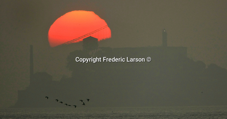 The Bay Bridge and Alcatraz Island where silhouetted by the rising sun that appeared out the low lying fog and haze during sunrise in San Francisco, California.