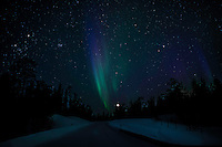 Cold crisp clear night looking down the road, at the moon and the northern lights. (Photo by Travel Photographer Matt Considine)