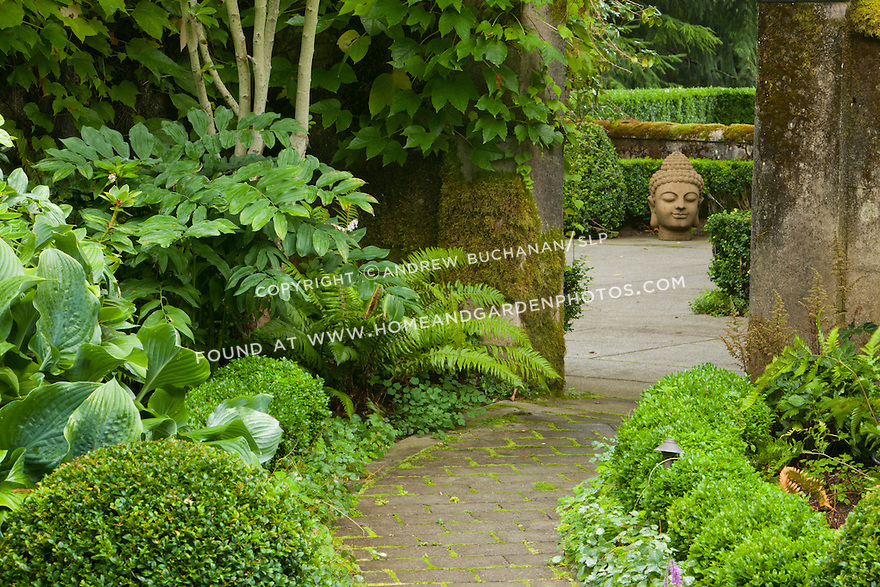 With a statue of buddha looking on, a brick pathway winds through a lush garden.