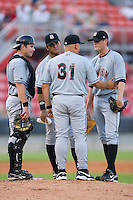 Birmingham Barons pitching coach J.R. Perdew #31 has a meeting on the mound with Adam Ricks #7, Javier Colina #41 and Kyle McCulloch #25 at Five County Stadium August 15, 2009 in Zebulon, North Carolina. (Photo by Brian Westerholt / Four Seam Images)