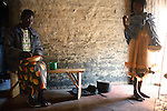 MPHANDULA, MALAWI - AUGUST 21: Ethel Dailesi, age 44, eats porridge for breakfast with her daughter Rebecca Masawo, age 10, in their living-room on August 21, 2006 in Mphandula village, about 30 miles outside Lilongwe, Malawi. Ethel was diagnosed with HIV/Aids in 2004 and has been on antiretroviral drugs since December 2005. She has just taken her medicine. She is often sick and her two daughters take care of her. Her children cook and clean for her. The girls attend a school nearby but they usually stay home when their mother is too sick. Mphandula is a poor village in Malawi, without electricity or clean water. Nobody owns a car or a mobile phone. Most people live on farming. About 7000 people reside in the village and the chief estimates that there are about five-hundred orphans. Many have been affected by HIV/Aids and many of the children are orphaned. A foundation started by Madonna has decided to build an orphan center in the village through Consol Homes, a Malawi based organization. Raising Malawi is investing about 3 million dollars in the project and Madonna is scheduled to visit the village in October 2006. Malawi is a small landlocked country in Southern Africa without any natural resources. Many people are affected by the Aids epidemic. Malawi is one of the poorest countries in the world and has about 1 million orphaned children. (Photo by Per-Anders Pettersson)