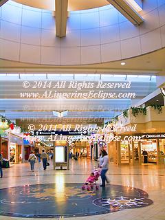 Minneapolis-Saint Paul International Airport Corridor of Shops next to the TSA Security Check-point.  Busy travelers walk under the skylight.