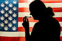 Man smoking a pipe with American marijuana flag i background, Littleton, Colorado USA.  Colorado was the first state to legalize the sale of marijuana for recreational use in 2014.