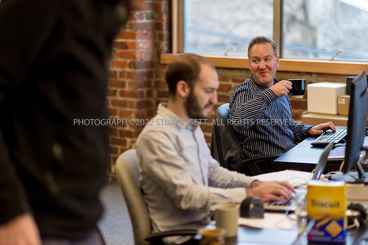 2/28/2014&mdash;Seattle, WA, USA<br /> <br /> Chris Hammersley, 42 (right), a Seattle based e-commerce executive, working and chatting at his desk at Office Nomads, a coworking space in Seattle&rsquo;s Capitol Hill neighborhood.<br /> <br /> Hammersley is based in Seattle, but his company HQ is in Walnut Creek, Ca. and his bosses live in Chicago and Boston. When meetings take place, they can happen anywhere, so Chris uses coworking spaces in those cities and others when he travels for work. <br /> <br /> <br /> Photograph by Stuart Isett. <br /> &copy;2013 Stuart Isett. All rights reserved.