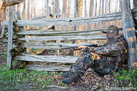Hunter in camouflage sitting by a wooden fence hunting wild turkey.