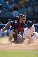 Shane Hoelscher (22) of the Asheville Tourists is tagged out at home plate by Rome Braves catcher Tanner Murphy (14) at McCormick Field on July 26, 2015 in Asheville, North Carolina.  The Tourists defeated the Braves 16-4.  (Brian Westerholt/Four Seam Images)