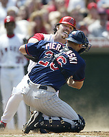 Scott Spiezio of the Los Angeles Angels is tagged by A.J. Pierzynski of the Minnesota Twins during a 2002 MLB season game at Angel Stadium, in Anaheim, California. (Larry Goren/Four Seam Images)