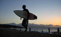 A surfer walks off the beach in Maui May 13,  2005 after surfing at sunset on the North shore of the Hawaiian island. (Alan Greth)
