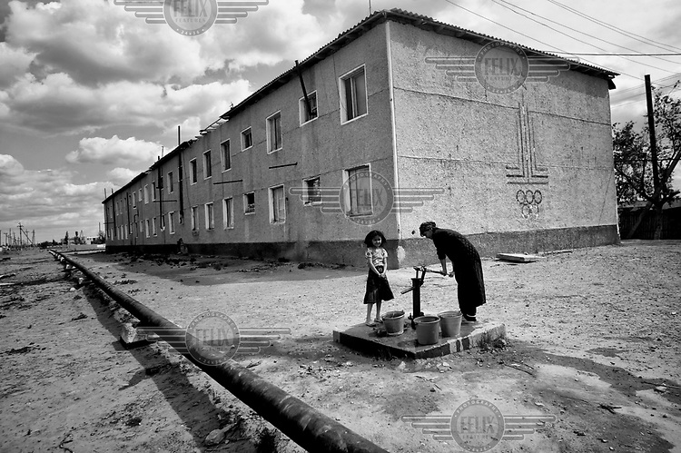 A woman pumps water fropm a standpipe beside an apartment block. On the wall is the fading emblem of the 1980 Moscow Olympic Games.  During the 1950s and the 1960s the rivers that feed the Aral Sea (the Amu Darya and the Syr Darya) were diverted for irrigating cotton and other crops. This caused the lake to shrink uncovering sediments heavily polluted with industrial fertilizers that were washed into the lake over the preceding decades. Without the lake's water to contain it these toxic particles were spread by the wind and have caused numerous health problems in surrounding communities. Furthermore, as the lake evaporated the remaining water became increasingly saline and unable to sustain life, destroying the fishing industry. Muynak, once a thriving fishing port, became a depressed and dusty town far from the receding shore.