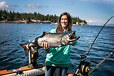 ALASKA, Ketchikan, a female fisherman shows off her catch while fishing the Behm Canal near Clarence Straight, Knudsen Cove along the Tongass Narrows