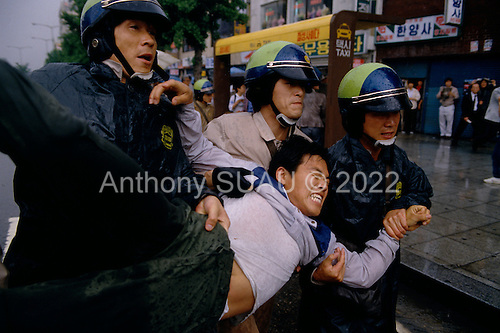 "Seoul, South Korea.May 1987..Arresting a student protester during a government crackdown on activists...After two decades of building an economic miracle, in the summer of 1987 tens of thousands of frustrated South Korean students took to the streets demanding democratic reform. ""People Power"" Korean-style saw Koreans from all social spectrums join in the protests...With the Olympics to be held in South Korea in 1988, President Chun Doo Hwan decided on no political reforms and to choose the ruling party chairman, Roh Tae Woo, as his heir. The protests multiplied and after 3 weeks Chun conceded releasing oppositionist Kim Dae Jung from his 55th house arrest and shaking hands with opposition leader Kim Young Sam. Days later he endorsed presidential elections and an amnesty for nearly 3,000 political prisoners. It marked the first genuine initiative of democratic reform in South Korea and the people had their victory."