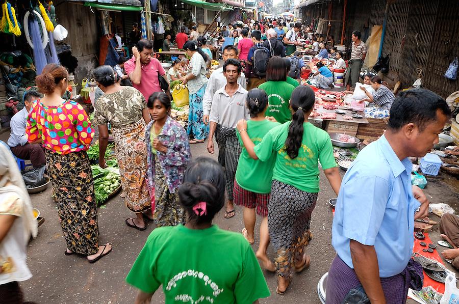 YANGON, MYANMAR - CIRCA DECEMBER 2013: People walking and wandering around the street market of Yangon.