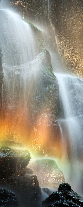 Rainbows and golden light illuminate this waterfall cascade in the Mt. Hood Wilderness.