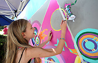 NWA Democrat-Gazette/DAVID GOTTSCHALK   Anais Bowerman, 11, works Thursday, July 13, 2017, on her portion of a mural on the east wall of the Arts Center of Ozarks in Springdale. Bowerman is participating in the Street Art My Heart program for ages six through fourteen. Students spent the week going from sketches to conception creating a mural on the center's exterior building wall. The students had the opportunity to work with guest artist Matt Miller on the project.