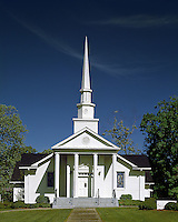 The exterior of the traditional architecture of a Baptist church with a prominent spire and columns. Dawsonville, Georgia.