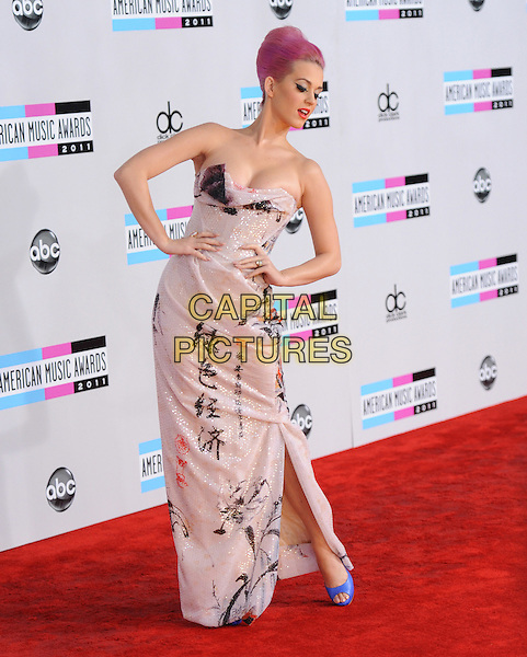 Katy Perry (wearing Vivienne Westwood).2011 American Music Awards - Arrivals held at Nokia Theatre LA Live, Los Angeles, California, USA..November 20th, 2011.ama amas ama's full length white Chinese sequins sequined draped dress strapless writing print blue peep toe snakeskin shoes cleavage hands on hips slit split looking down posing.CAP/RKE/DVS.©DVS/RockinExposures/Capital Pictures.