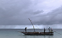 A dhow sets out to sea without it distinctive triangular sail deployed. Zanzibar, Tanzania. July 1997