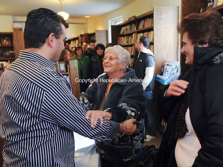 """WASHINGTON, CT 25 NOVEMBER- 112512JS03- Television personality and author Buddy Valastro gets a hug and smile from Clara Caliando of Plainville, center, as her daughter Carol Lemieux, right, looks on as he autographs copies of his book """"Cooking Italian with the Cake Boss"""" Sunday at the Hickory Stick Bookshop in Washington. After the book signing, Valastro has a show at the Warner Theatre in Torrington. .Jim Shannon Republican American"""