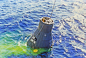 "The Mercury-Atlas 6 ""Friendship 7"" spacecraft is retrieved from the Atlantic Ocean following astronaut John H. Glenn Jr.'s three-orbit space mission on February 20, 1962.  In this view, the capsule is still in the water, with retrieval cable connected to it.Credit: NASA via CNP"
