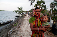 Namita with her baby stands on a dam by a river in Sunderbans. Her husband is in Kolkata to work as a daily labourer. People here in Sunderbans go to big cities for better fortune as Sundarban area lacks infrastucture and work facilities. Sunderbans, West Bengal, India. Arindam Mukherjee