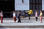 Children playing physical game with strings; exercise; small rural village near Wuxi; rural China; 042403