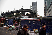 Workers demolish old buildings behind a market in Urumqi, Xinjiang, China.