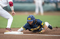 Michigan Wolverines outfielder Jordan Brewer (22) dives back to first base during Game 6 of the NCAA College World Series against the Florida State Seminoles on June 17, 2019 at TD Ameritrade Park in Omaha, Nebraska. Michigan defeated Florida State 2-0. (Andrew Woolley/Four Seam Images)