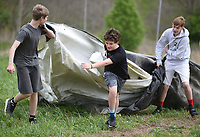NWA Democrat-Gazette/DAVID GOTTSCHALK Connor Hinton (center), an eighth grade student at The New School, moves plastic tarps Thursday, April 11, 2019, with other seventh and eighth grade students from the school during a service project at Cobblestone Farms in Fayetteville. Cobblestone Farms is a non profit that donates half of the food grown to food insecure families in the northwest Arkansas area.