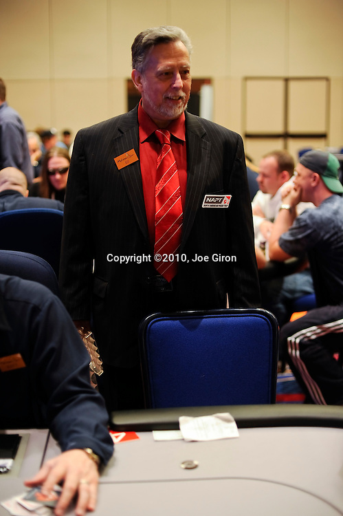 A member of the tournament floor staff has a chuckle while he waits for Paul Aurélien's last chip to be blinded off.  He was about to break the table but then paused because he didn't want to move one chip.