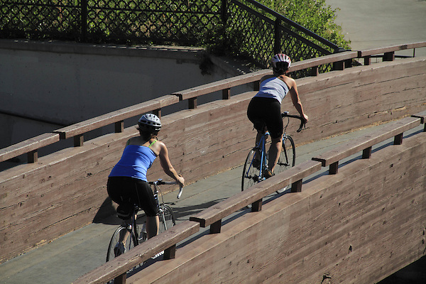 Two women biking over a bridge in Confluence Park, Denver, Colorado, USA. .  John offers private photo tours in Denver, Boulder and throughout Colorado. Year-round.