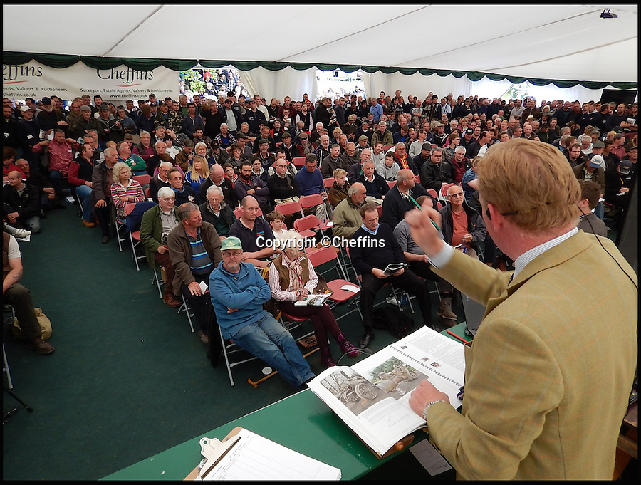 BNPS.co.uk (01202 558833)<br /> Pic: Cheffins/BNPS<br /> <br /> Big crowds for the auction.<br /> <br /> A treasure trove of vintage tractors and steam engines collected by two enthusiasts have sold for a massive £1.5 million.<br /> <br /> John Keeley and his wife May amassed the hoard of rusty machines on their farm in Berkshire over a 40 year period.<br /> <br /> Their bizarre fleet included 50 vintage tractors and 15 steam engines and was so vast they were able to stage their own agricultural show that became a famous event.