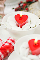 Bowls of heart-shaped candles surrounded by white dragees decorate the dining table