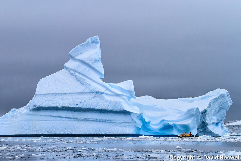 A group of passengers on a zodiac cruise near Pleneau Island along the Antarctic Peninsula.