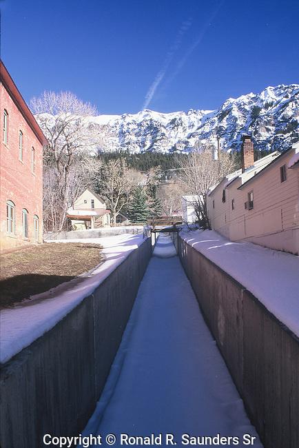BRIDGE OVER SNOW COVERED STREAM IN COLORADO MOUNTAIN TOWN