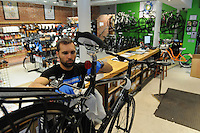 NWA Media/ J.T. Wampler - John Robertson of Bentonville builds a road bike Monday Dec. 22, 2014 at Phat Tire Bike Shop in Bentonville. The shop has seen an increase in bike sales in the last weeks before Christmas with children's bikes being the majority of the sales.