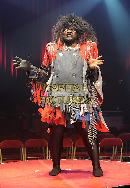 Le Gateau Chocolat.Performing at a press call to promote 'La Soiree', a new unique theatre show with a heady cocktail of cabaret, new burlesque and circus sideshows, Roundhouse, London, England..24th November 2011.stage performance performing full tights length black jacket grey gray red tassels fringed wig hands arms.CAP/BEL.©Tom Belcher/Capital Pictures.