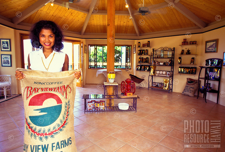 Roz Roy, owner of Bay View Farms, holding Kona coffee bag in the visitor's center, Kealakekua