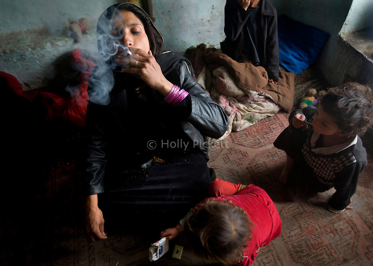 "Surrounded by her children, Karima, 30, smokes heroin and opium in her one-room home in the neighborhood of Shahre Kohneh, roughly translated as ""Broken City,"" Kabul, Afghanistan, Monday, Apr. 6, 2009. Karima is addicted to heroin, opium and hashish, and an outreach team from the Nejat Center, a community-based drug treatment program funded by the United Nations Office on Drugs and Crime, has been trying to convince her to quit. A United Nations survey begun this month is widely expected to show that at least one in 12 Afghans abuses drugs -- double the number in the last survey four years ago."