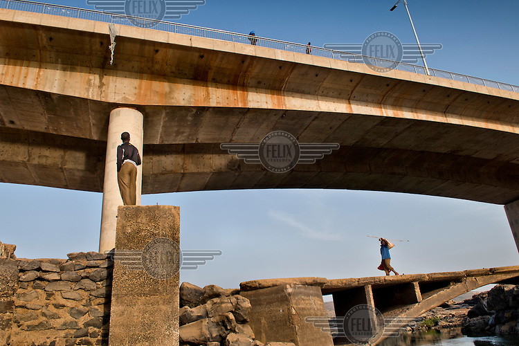 People walking on a beneath a Chinese built bridge spanning the River Niger. The bridge was opened in September 2011 and is the third crossing of the Niger in Bamako.