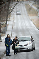 Jeff Mincy helps Rosie Morales Saturday, Jan. 11, 2020, after her car became stuck in ice as she drove up Wilson Street while on her way to work. Sleet fell in Northwest Arkansas for part of the day, creating difficulty for drivers. Check out nwaonline.com/200112Daily for today's photo gallery. (NWA Democrat-Gazette/Andy Shupe)