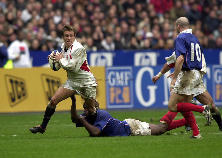 Photo.Richard Lane.France v England at Stade de France. 2-3-2002. Lloyds TSB Six Nations Championship..Jonny Wilkinson is tackled by Serge Betsen.