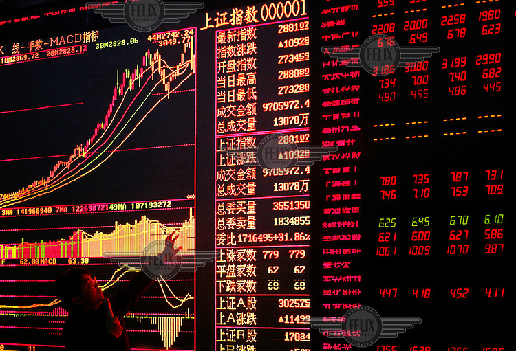 A portfolio manager speaks to investors to explain the recent slide and rebound in the Shanghai Index while standing in front of a trading board at a local securities exchange house.